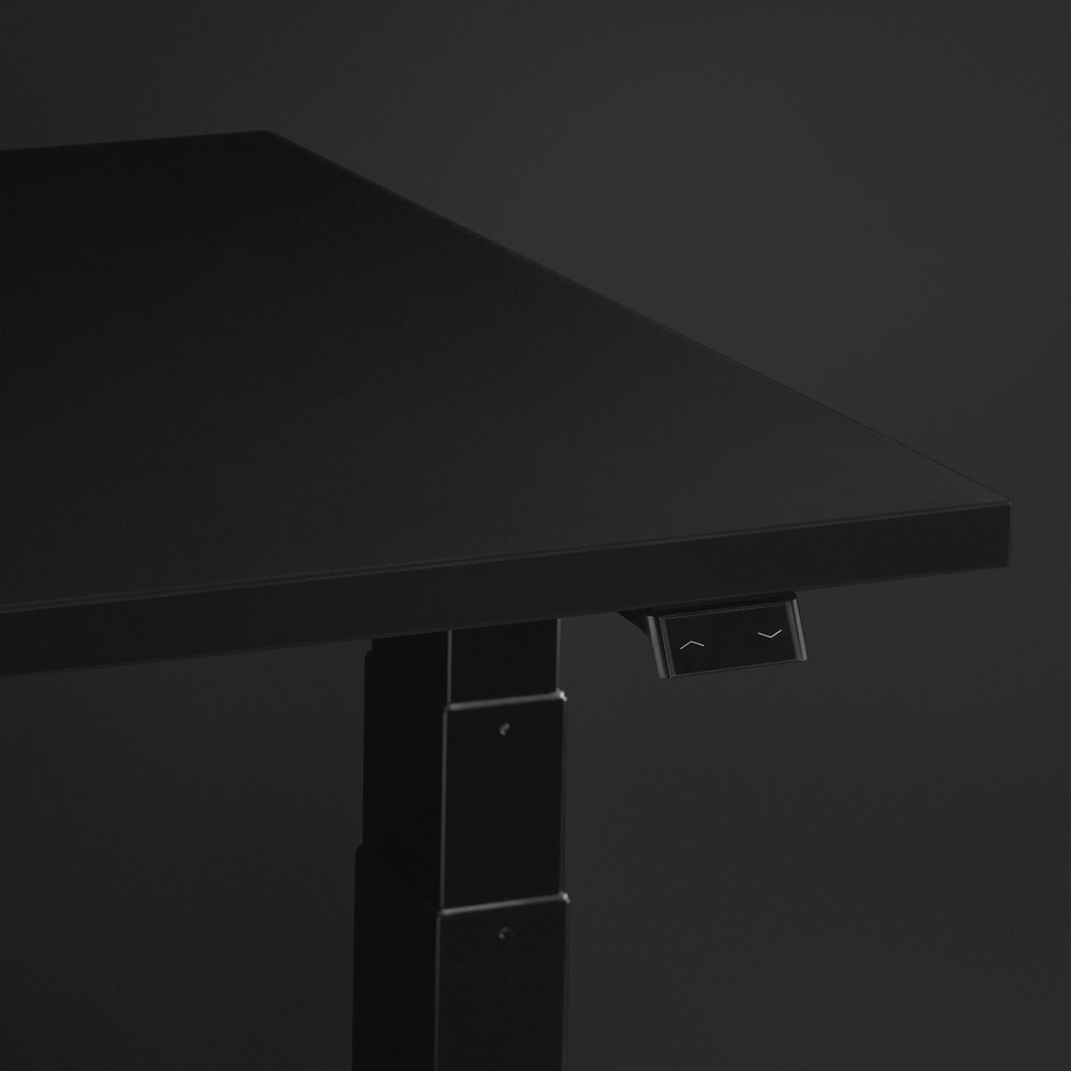 Nevi Gaming Desk surface close-up featuring the easy-touch adjustment switch with dark grey background