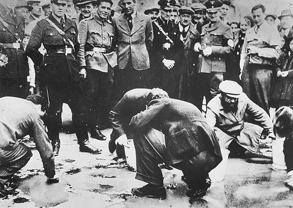 Austrian Nazis and local residents look on as Jews scrub the pavement.