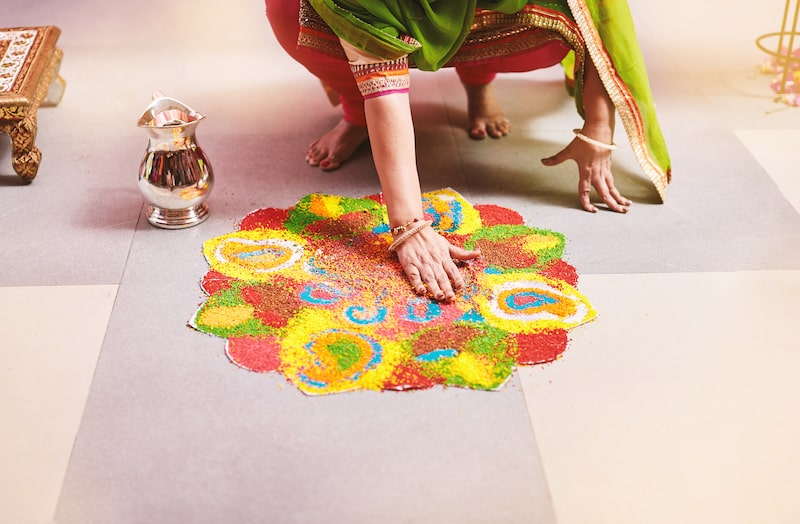 An intricate Rangoli pattern being created on the floor of a home