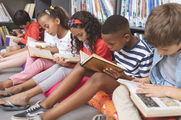Children sat in a row reading books in a library