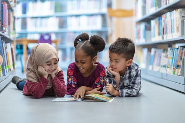 Three children reading a book together