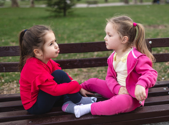 Two girls sitting on a bench facing each other and talking