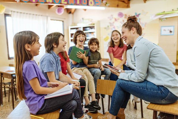 Teacher chatting to smiling children in classroom