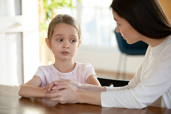 Young child looking upset and talking to female adult