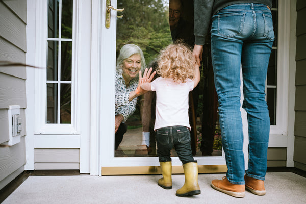 Child seeing older person through window social distancing