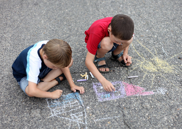 Two boys drawing with chalk on the pavement