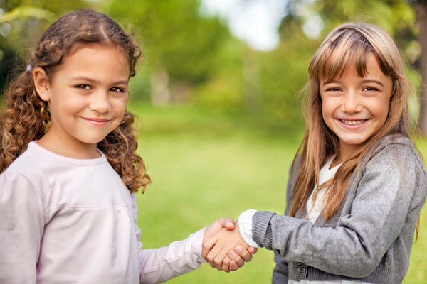 Two girls smiling and shaking hands