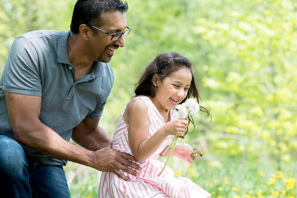 Child and parent playfully blowing dandelions