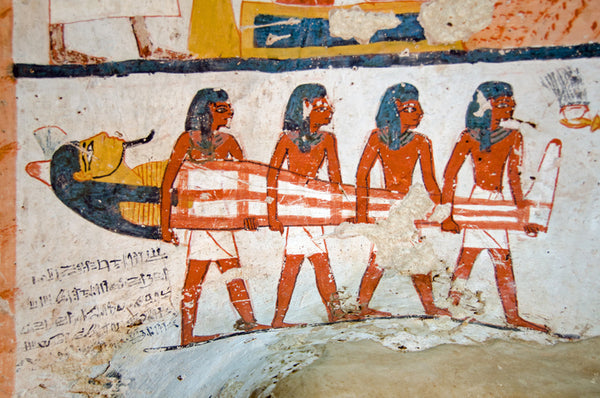 Mural of four ancient Egyptian men carrying a mummy