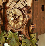 The Dial of a Schneider Black Forest Cuckoo Clock with roman numerals, Green Leaves and a carved Bird