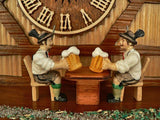 Two Bavarian men in Lederhosen drinking Beer under the dial on Schneider Black Forest Cuckoo Clock