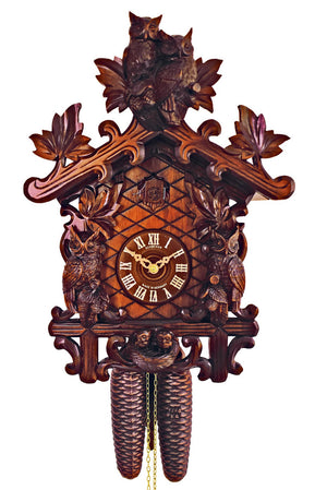 Two Owls sitting on Top of a Anton Schneider 8 Day Traditional Black Forest Cuckoo Clock looking right at you. Two more Owls are framing the Dial of the clock above the little nest with two baby Owls.