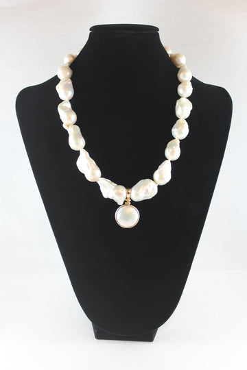 Baroque pearl strand with round mabe pearl