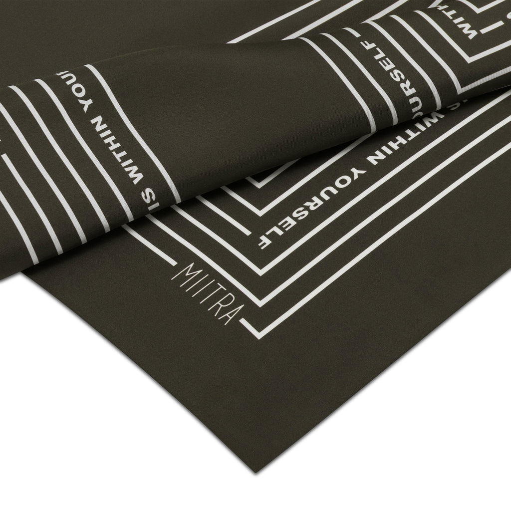 Close up view of the MIITRA logo on an olive brown silk scarf