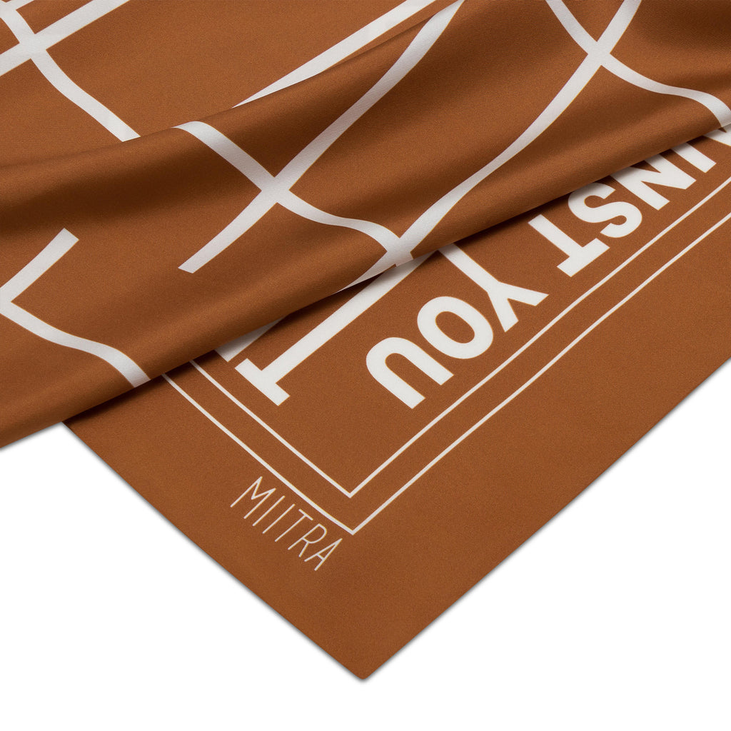Close up view of the MIITRA logo on a brown silk scarf