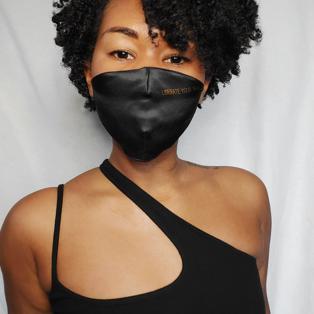 Woman wearing a black silk face mask that says liberate your mind on it