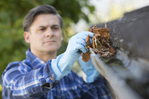 Man Clearing Leaves From Guttering Of House - prepare your home for winter
