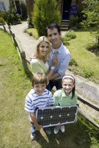 Family of four outdoors with solar panel, portrait, elevated view