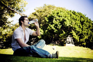 Young man sitting in the park and drinking water from the bottle. - summer heat