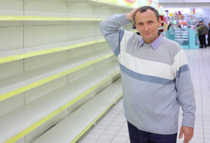 elderly man at empty shelves in  shop scratches in  nape
