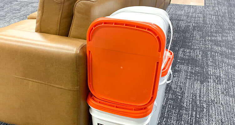 emergency food buckets stacked behind a couch