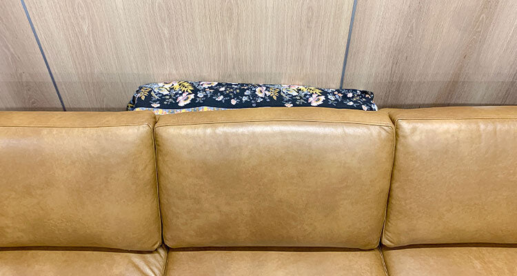 buckets covered with cloth behind a couch, front view