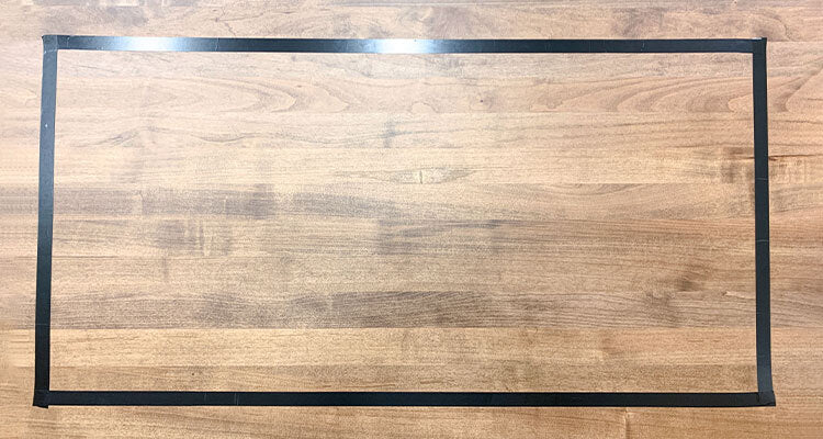 wood surface with a rectangle of electrical tape