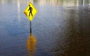 Crosswalk sign surrounded by high flood water.