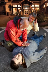 Older man oerforming CPR on a young man.