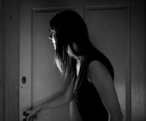 black and white photo of a young woman opening a door