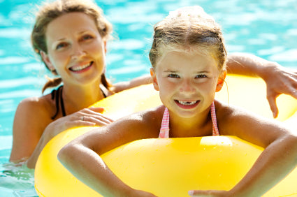 Mother and daughter swimming in pool with inner tube