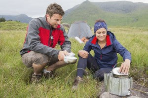Couple cooking outside on camping trip in the wilderness