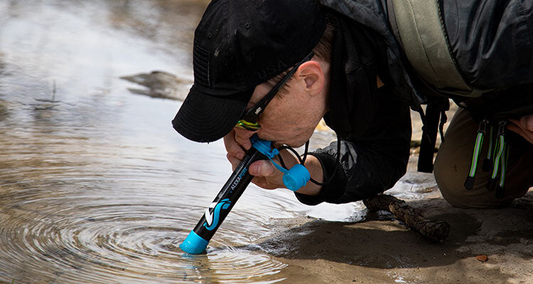 man drinking water from river using survival spring filter straw
