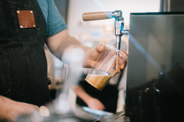 Barista pouring large cup of nitro cold brew coffee