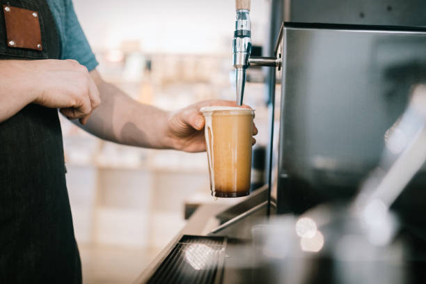 Barista just finished pouring large glass of nitro cold brew coffee