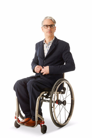 model wears navy dress pants for wheelchair users