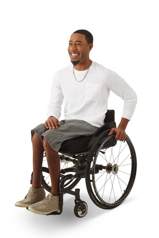 wheelchair model wearing men's adaptive denim shorts