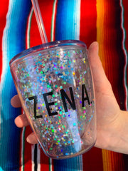 the Zena sparkly cup close up with a hand around it to show the size. Colourful background