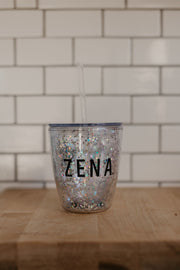 Sparkly cup with a straw that says ZENA on it. There is lots of glitter in the cup and perfect for margaritas