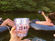 The Zena glitter cup photographed in a disposable camera feel in front of a scene with friends tubing down the  river Nile having fun and taking photos.