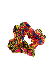 Close up image of a bright kitenge material handmade scrunchie made in uganda from locally sourced and patterned fabric