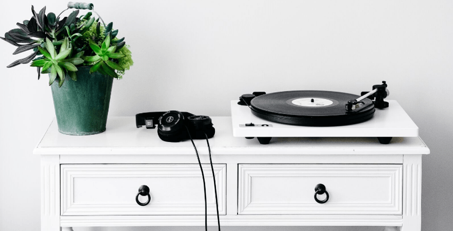 White Orbit Custom on a white table with Grado headphones and a plant