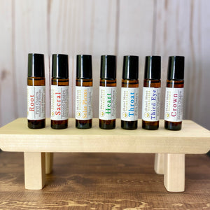 7 Chakras 10ml Aromatherapy Roll On Bottles left to right: Root, Sacral, Solar Plexus, Heart, Throat, Third Eye, Crown. 10ml Amber Glass Roll On bottles with Black lids.