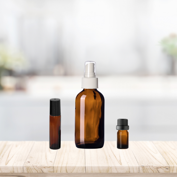Amber Glass Bottles on Wooden Shelf to show relative bottle sizes. From Left to right: 10ml Amber Glass Roll On; 4oz Amber Glass Spray Bottle with White Spray Cap; 5ml Amber Glass Essential Oil Bottle with black Euro dropper cap.