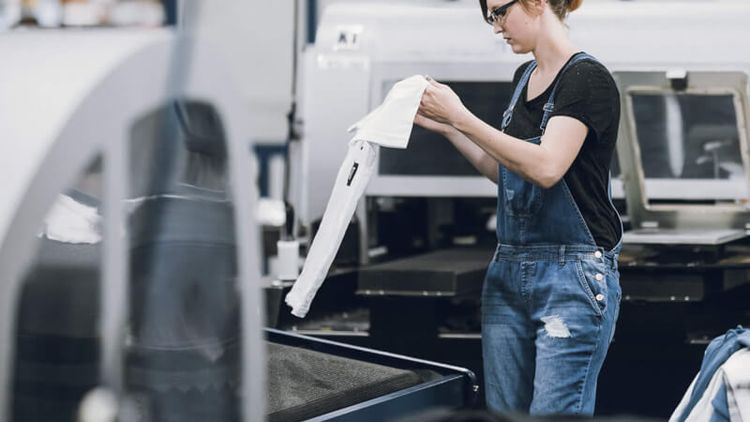 A woman picking up shirt after finishing printing