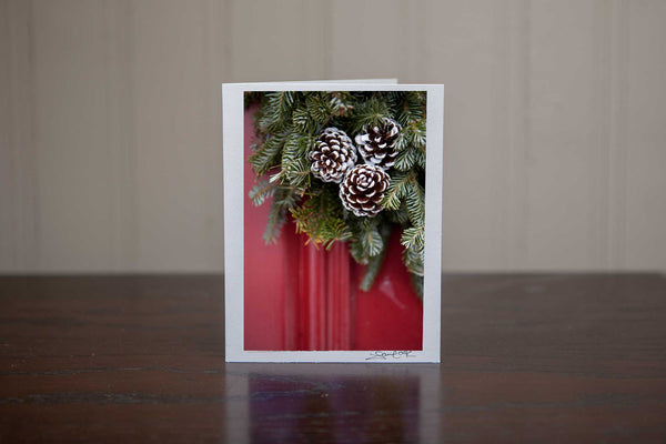 Greeting card featuring 'Adorn' a photograph of a red door with close up of a Christmas wreath of evergreen trees and pinecones on the door Photo by Cambridge Ontario Photographer Laura Cook of Vision Photography