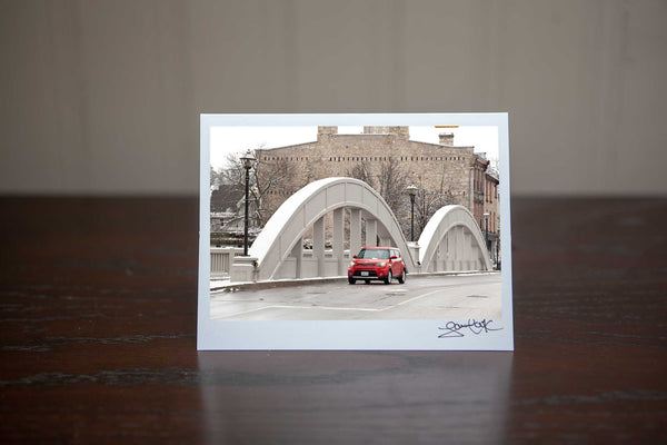 Christmas Greeting Card featuring ' Cambridge Soul'  a photograph of Downtown Galt Cambridge Main St Bridge with a red Kia Soul driving over the bridge Photo by Cambridge Ontario Photographer Laura Cook of Vision Photography