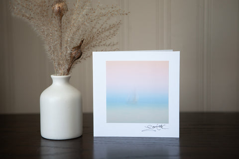 "photo greeting card featuring Lara Cook's original creation 'Peaceful Abandon"" which is a sailboat on the lake with a cotton candy sky it is a photo-impressionist photograph so the boat is blurred to give the essence of the scene and the emotion felt."
