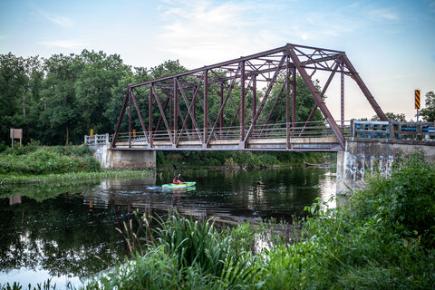 Paddling a Kayak Speed River under black bridge in Hespeler, Cambridge photo by Laura cook of Vision Photography