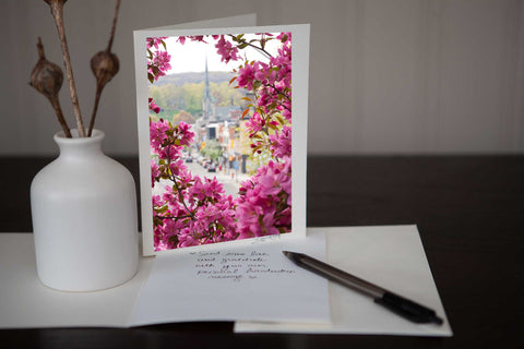 "photo greeting card featuring the original photograph ""Spring on Main"" which is a view of Main Street downtown Galt encircled by spring flower blossoms by photographic artist Laura Cook"